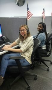 two employees taking calls in their call center booths