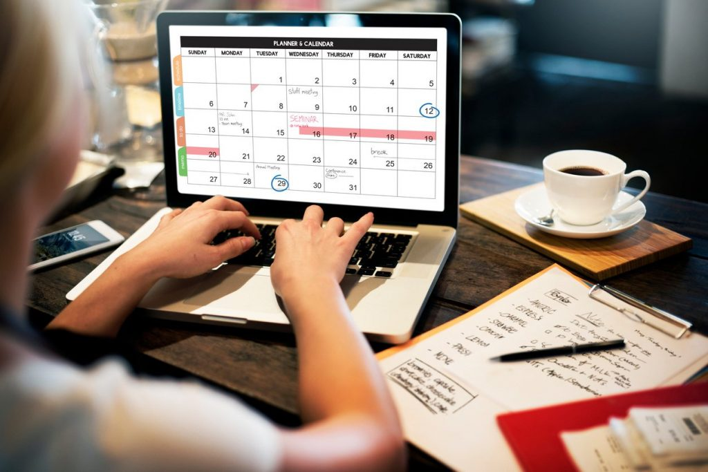 person working on their calendar on a laptop
