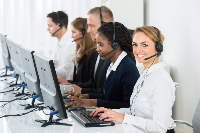 five employees ready to take client calls for the day