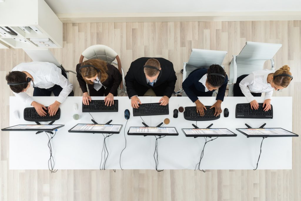 five workers typing on keyboards