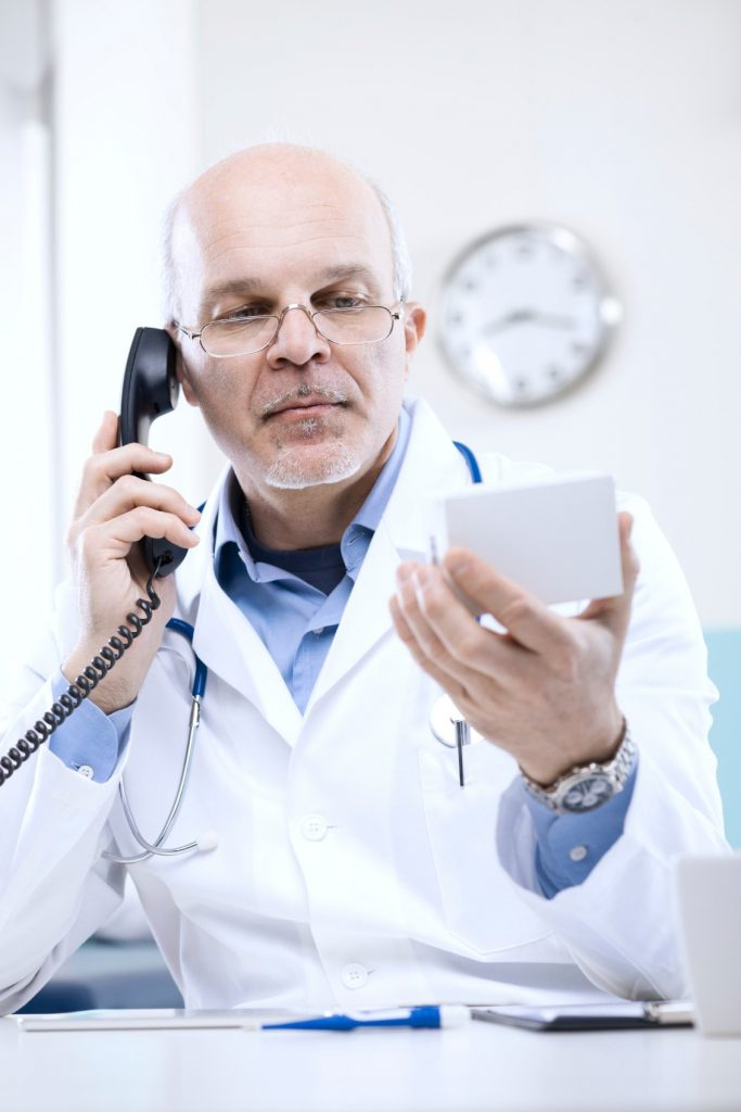 Doctor taking a call on the phone and looking at something he's holding
