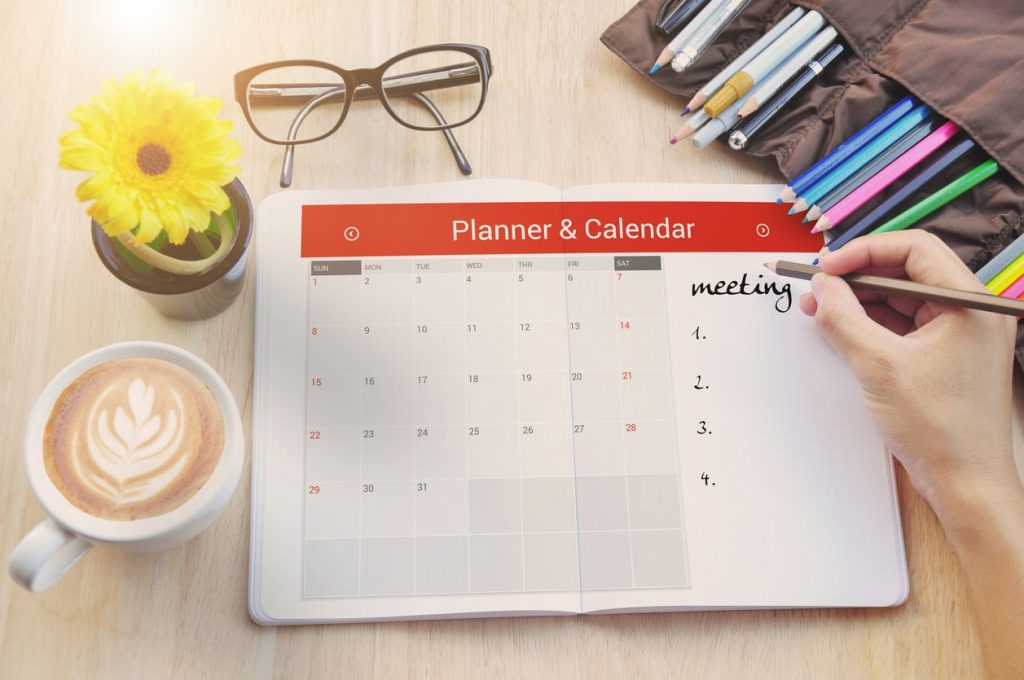 person filling out their calendar with a pencil