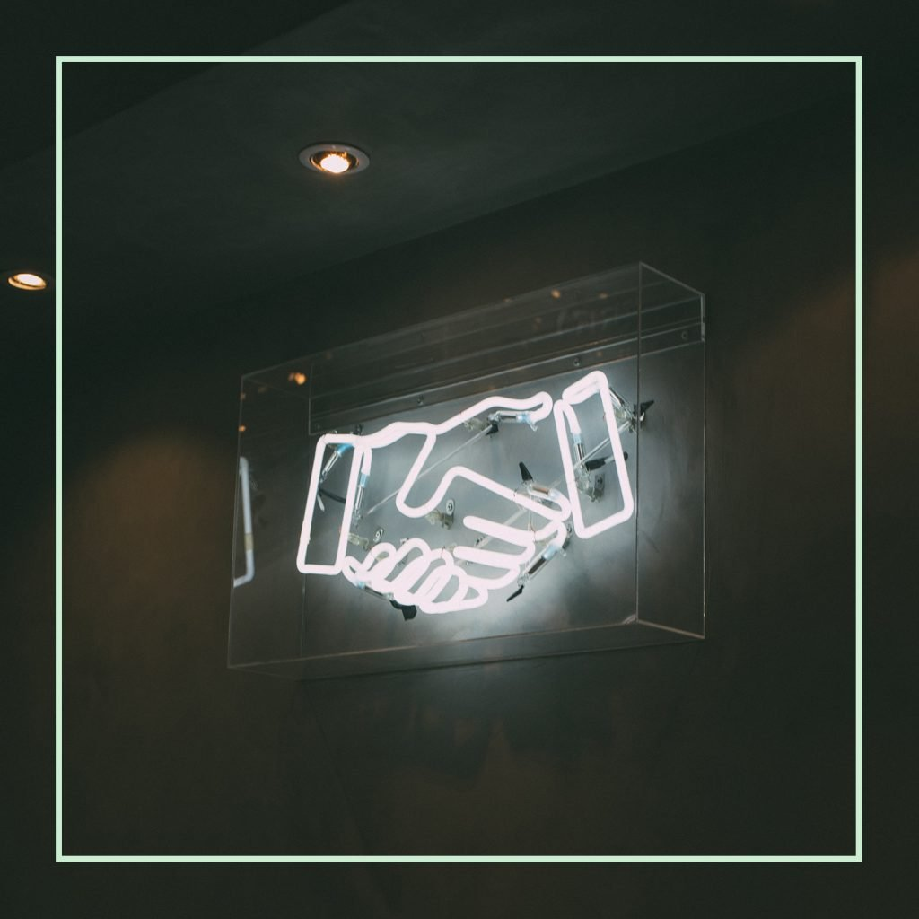 Light up sign of two hand shaking