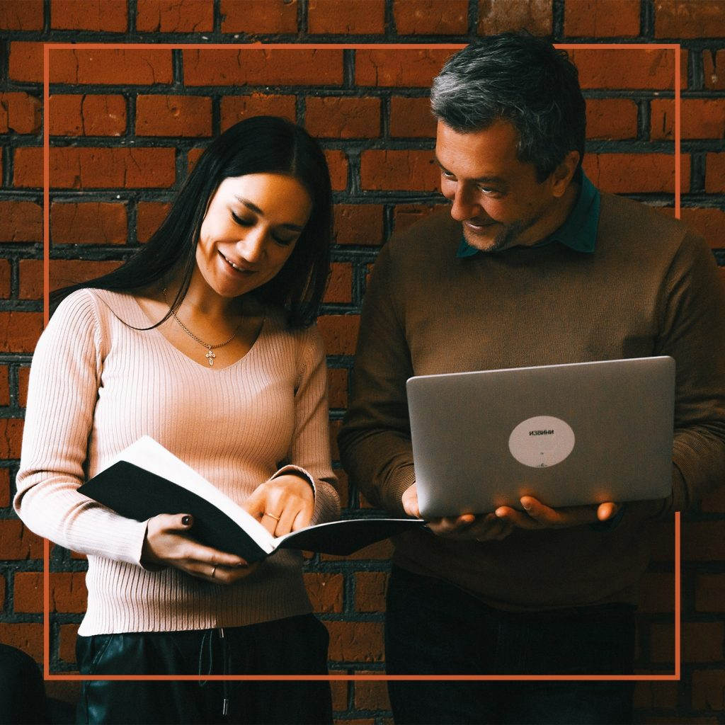 man standing with a laptop next to girl holding a book