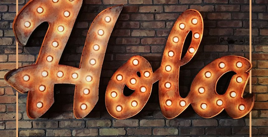 Light up sign against a brick wall that says hola